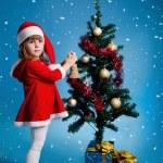 Amusing Santa girl decorating Christmas tree — Stock Photo