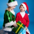 Stock Photo: Girl and boy in Christmas costumes playing with gifts