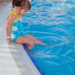 Stock Photo: Cute little girl sitting near the swimming pool