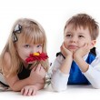 Adorable boy and the girl smelling a flower — Stock Photo
