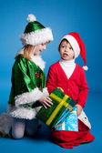Girl and boy in Christmas costumes playing with gifts — Stock Photo