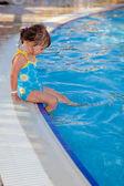 Cute little girl sitting near the swimming pool — Stock Photo