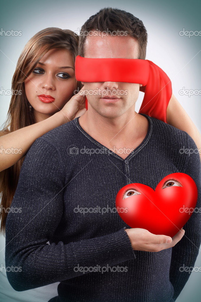 Woman blindfolding a man holding his open eyes heart in his hand    #4943830