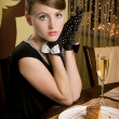 Stock Photo: He young girl sits with a glass of champagne and a pie slice