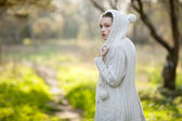 The girl in a white sweater walking on autumn park, has looked back on the — Stock Photo