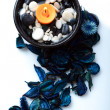 Orange candle and a blue potpourri — Stock Photo