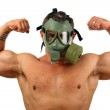 Man in gas mask showing muscles — Stock Photo