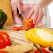 Tomato cutting on a wooden plate — Stock Photo