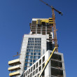 Stock Photo: Elevating crane and building