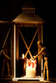A jointed doll warming up on three candles in a lantern. — Stock Photo
