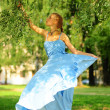 Stock Photo: Young girl in a blue dress in the park