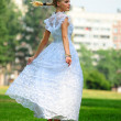 Stock Photo: Girl in white dress posing in the park