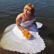 bride dressed in wedding gown in water — Stock Photo