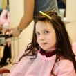 Stock Photo: The little girl doing a hairdress