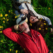 Stock Photo: Happy couple lying on a grass