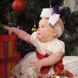 Baby girl and Christmas tree — Stockfoto