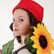 Girl in red hat with sunflowers in their hands - Stock Photo