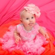 Baby girl wearing pettiskirt tutu and pearls crawling - Stock Photo