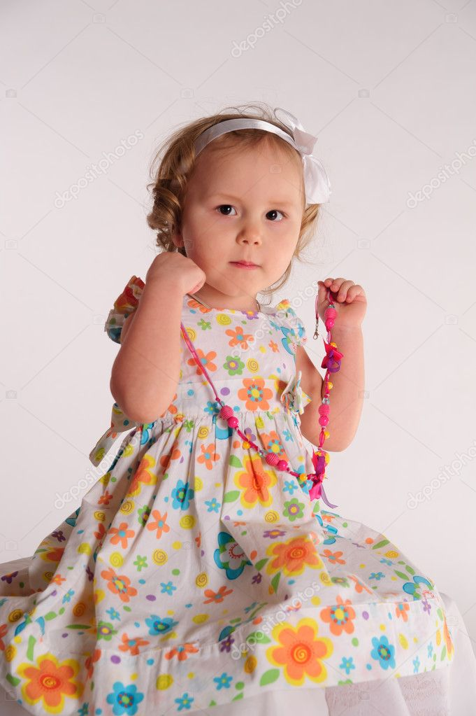 Baby girl in beautiful dress trying necklace on herself  Stock Photo #5272233