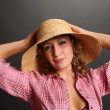 Stock Photo: Portrait of a cute young woman wearing a straw hat