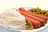 Dish with sausage, noodles and green peas — Stock Photo