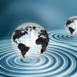 Globes on water ripples — Stock Photo