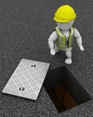 Builder inspecting drains through manhole cover — 图库照片