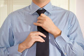 A young man getting dressed to work. — Foto de Stock