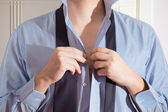 A young man getting dressed for work. — Stock Photo