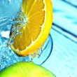 Orange and apple in water splash — Stock Photo