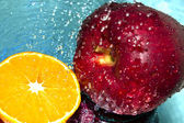 Apple and orange in water drops — Stock Photo