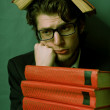 Sad young man with a stack of red books — Stock Photo