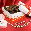 Stock Photo: Box of chocolates with present and pearls.