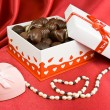 Box of chocolates with present and pearls. — Stock Photo