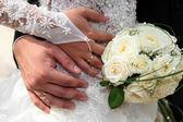 Nevěsta a ženich ruce snubní prsteny a kyticí růží — Stock fotografie