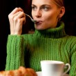 Young woman with a spoon in her mouth making breakfast with a cup of cappuc — Stock Photo #4829236