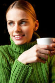 Portrait of young woman holding a cup of cappuccino — Stock Photo