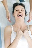Unga kaukasiska kvinna liggande leende och får huvudmassage — Stockfoto