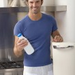 Man in the kitchen with a bottle of milk — Stock Photo
