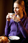 Young woman drinking cappuccino at breakfast — Stock Photo
