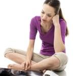 年轻女子坐在地上读一本杂志上白色背景斯图 — 图库照片