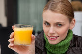 Young woman holding a glass of orange juice and looking at camera — Stock Photo