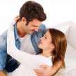 Couple embracing on the couch — Stock Photo