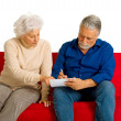 Elderly couple on the couch writing — Stock Photo