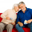 Elderly couple on the couch with money in hand — Stock Photo
