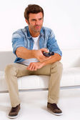 Single man on the couch watching TV — Stock Photo