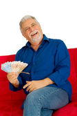 Elderly man on the couch with money in hand — Stock Photo