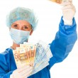 Female surgeon holding banknotes — Stock Photo
