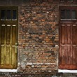 Two old wooden doors in brick wall — Stock Photo