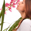 Beautiful young woman smelling orchid flower - Stock Photo